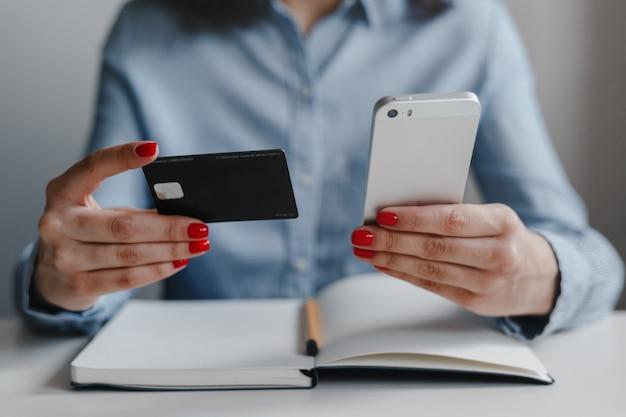 Nahaufnahme der hände der frau mit den roten nägeln, die kreditkarte und handy halten, die zahlung online tragen, die blaues hemd trägt.