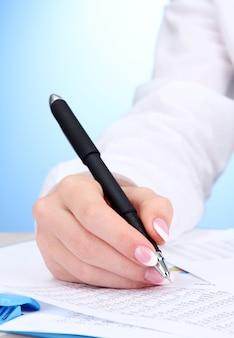 Nahaufnahme der hände der geschäftsfrau, die auf papier schreiben