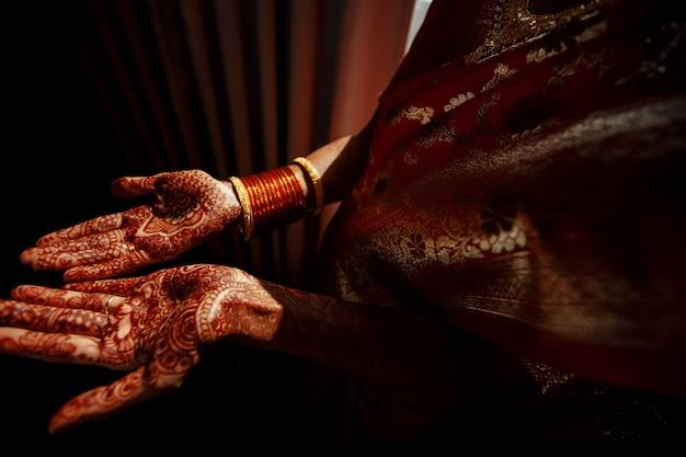 Nahaufnahme der hände der hindischen braut bedeckt mit hennastrauchtätowierungen