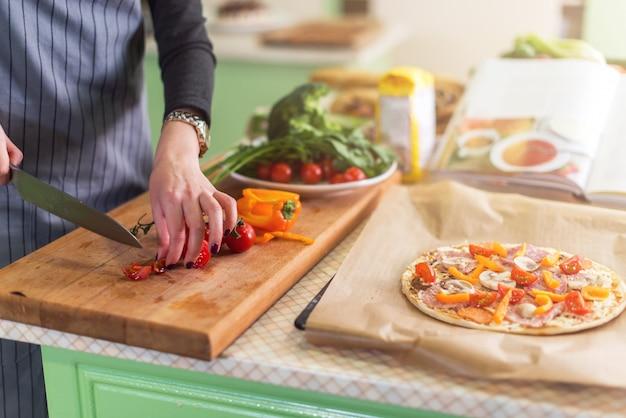 Nahaufnahme der hände der jungen frau, die gemüse an bord für pizza gemäß rezeptbuch schneiden