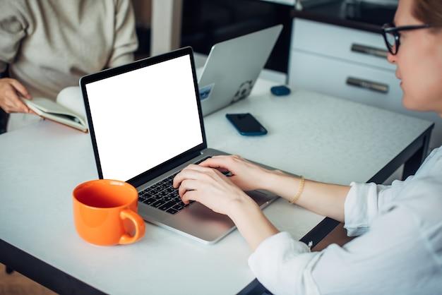 Nahaufnahme der hände der kaukasischen frau, die auf laptoptastatur schreiben. leerer bildschirm, platz für text. unscharfer hintergrund.
