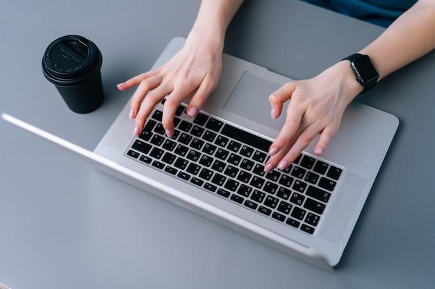 Nahaufnahme der hände der nicht erkennbaren geschäftsfrau, die auf der laptoptastatur sitzt, die am schreibtisch auf dem hintergrund des fensters im büroraum, selektiver fokus, kaffeetasse sitzt.