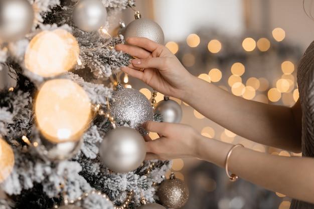 Nahaufnahme der hände der zarten frau, die ein silbernes spielzeug auf weihnachtsbaum setzen