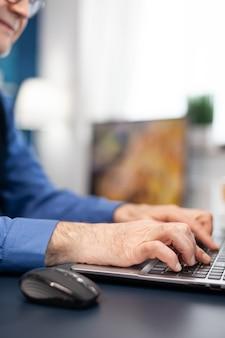 Nahaufnahme der hände des älteren mannes, die auf der laptop-tastatur tippen