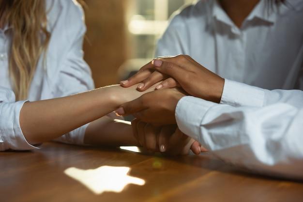 Nahaufnahme der hände des afroamerikaners und des kaukasischen menschen, die auf holztisch halten. weibliche hände, die sich in geste der freundschaft, einheit, familie, teamarbeit oder frauenrechte, erfolg, helfende hand berühren.