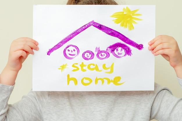 Nahaufnahme der hände des kindes, die ein bild der familiensilhouette unter dem dach und die worte stay home halten, die ihr gesicht bedecken. kinder im quarantänekonzept.