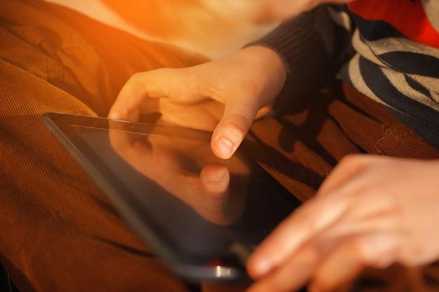 Nahaufnahme der hände des kindes schließen, digitale tablette für das spielen hochhalten