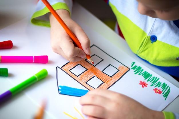 Nahaufnahme der hände des kleinen kinderjungen, der haus mit farbstiften zeichnet