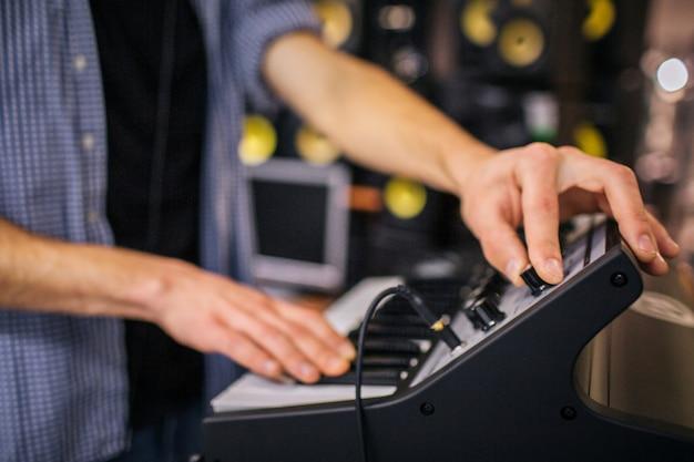 Nahaufnahme der hände des mannes auf der tastatur. guy schaltet den ton ein. er steht im zimmer. viele lautsprecher stehen hinter ihm.