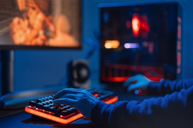 Nahaufnahme der hände des profispielers auf der tastatur in neonfarbe