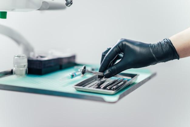 Nahaufnahme der hände des zahnarztes in den handschuhen, die zahnmedizinisches werkzeug wählen.