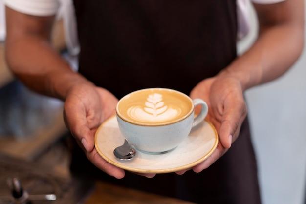 Nahaufnahme der hände, die kaffee halten