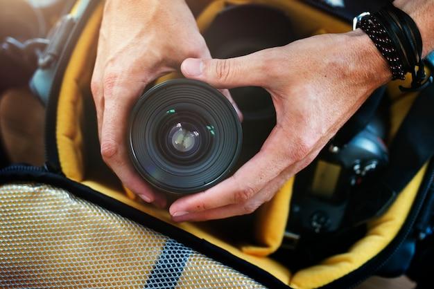 Nahaufnahme der hände, die kameraobjektiv von der tasche erhalten
