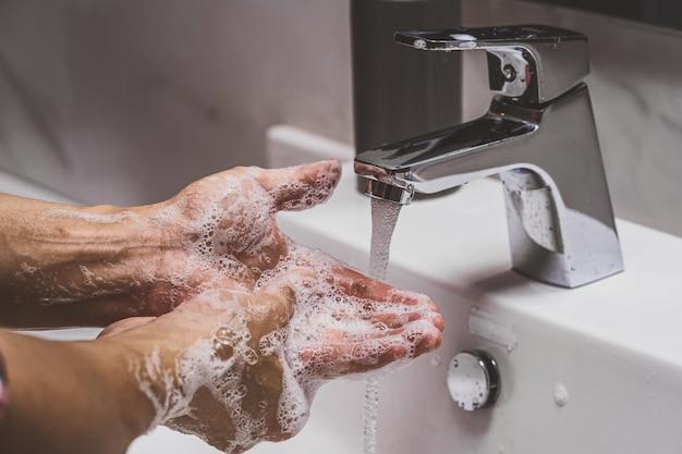 Nahaufnahme der hände, die mit chromwasserhahn und seife für die coronavirus-pandemie waschen