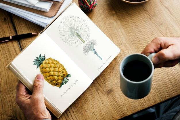 Nahaufnahme der hände, die offenen roman und kaffeetasse halten