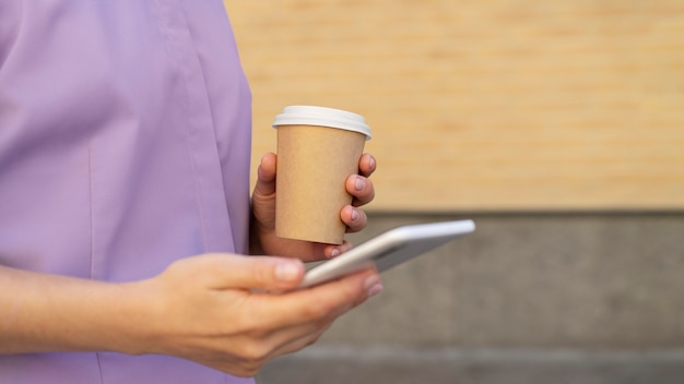Nahaufnahme der hände, die telefon und kaffeetasse halten