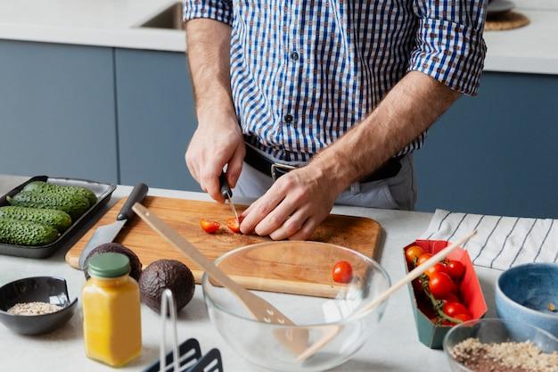 Nahaufnahme der hände, die tomaten schneiden