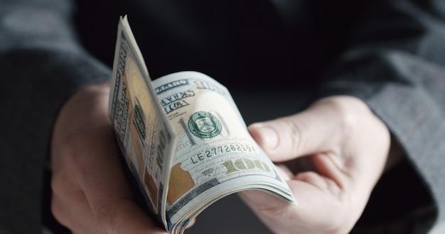 Nahaufnahme der hände, die us-dollar-banknoten mit 100 stückelung zählen
