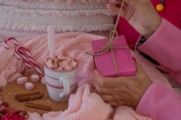 Nahaufnahme der hände einer frau in rosa pyjamas, die ein geschenkpaket öffnet, in ihrer nähe eine tasse mit heißem kakao mit marshmallows und zimtpulver. weihnachtsferien und glückliches menschenkonzept