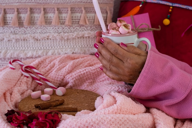 Nahaufnahme der hände einer frau in rosa pyjamas, die eine heiße schokolade mit marshmallows in einer keramiktasse halten. feiertage und menschenkonzept