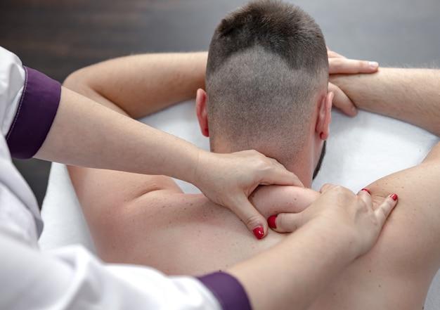 Nahaufnahme der hände einer massagetherapeutin beim kneten