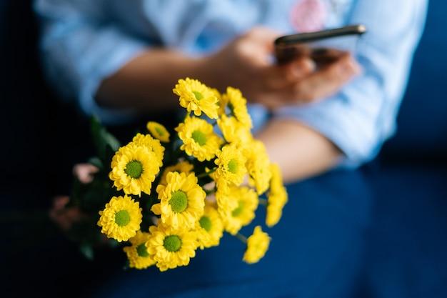 Nahaufnahme der hände einer nicht erkennbaren frau, die gelbe chrysanthemen des blumenstraußes hält und handy benutzt