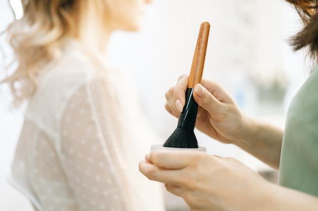 Nahaufnahme der hände einer nicht erkennbaren make-up-künstlerin, die puder mit make-up-pinseln hält