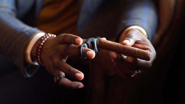 Nahaufnahme der hände eines afroamerikaners. in den händen einer afroamerikanischen zigarrennahaufnahme