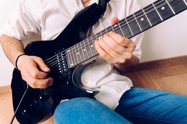 Nahaufnahme der hände eines gitarristen, der ein lied beim drücken der schnüre durchführt
