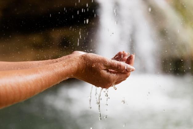 Nahaufnahme der hände eines jungen erwachsenen am wasserfall