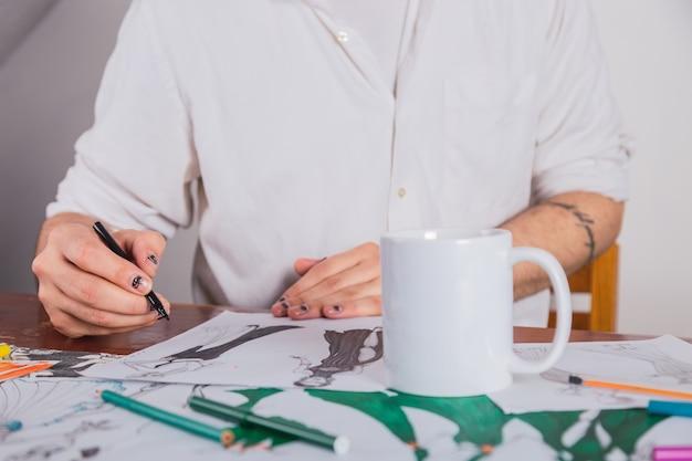 Nahaufnahme der hände eines jungen modedesigners, der kleider in seinem atelier skizziert.
