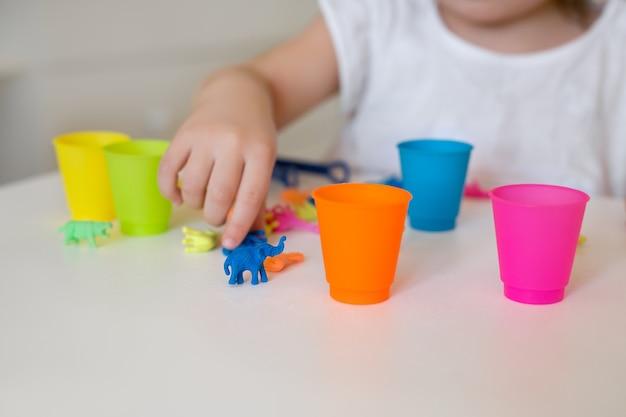 Nahaufnahme der hände eines kindes, die mit bunten tierfiguren und tassen spielen.