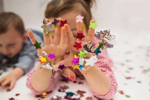Nahaufnahme der hände eines kindes in konfetti auf einem weißen hintergrund