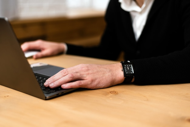 Nahaufnahme der hände eines mannes, die auf einer laptop-tastatur tippen. beschnittenes bild eines jungen mannes, der an seinem laptop in einem café arbeitet