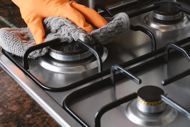 Nahaufnahme der hände in gummihandschuhe reinigung kochfeld