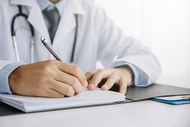 Nahaufnahme der hände männlichen doktors, die kenntnisse nehmen oder die medizinische karte des kunden ausfüllen oder medikation vorschreiben.