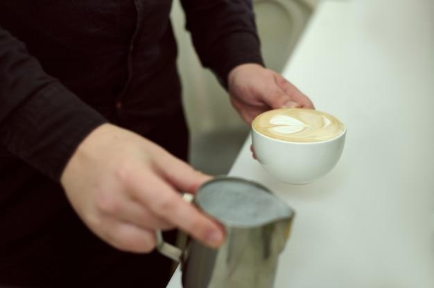 Nahaufnahme der hände von baristas, die in einer hand eine tasse kaffee und in der anderen milch halten