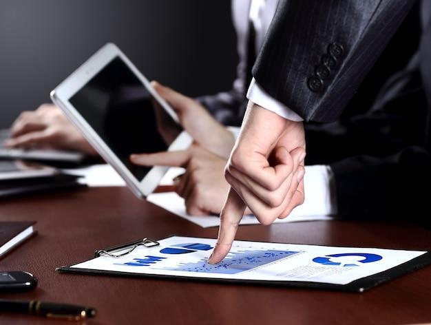 Nahaufnahme der hände von managern, die diagramm diskutieren und am tisch sitzen sitting