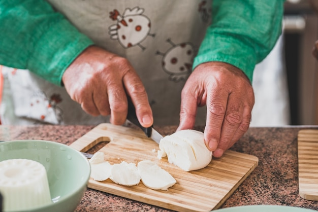 Nahaufnahme der hände von reifer mann und senior, die einen mozzarella mit einem messer schneiden und essen kochen?