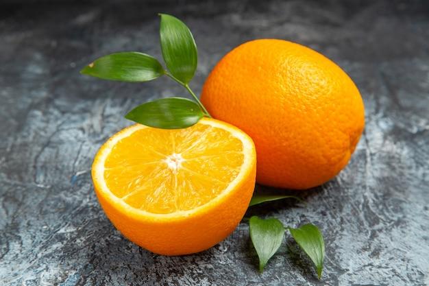 Nahaufnahme der halbierten und ganzen frischen orange mit blättern auf grauem hintergrund stockfoto