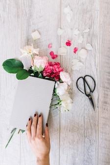 Nahaufnahme der hand buch mit hortensie und rosenblumen und -schere auf hölzerner planke halten
