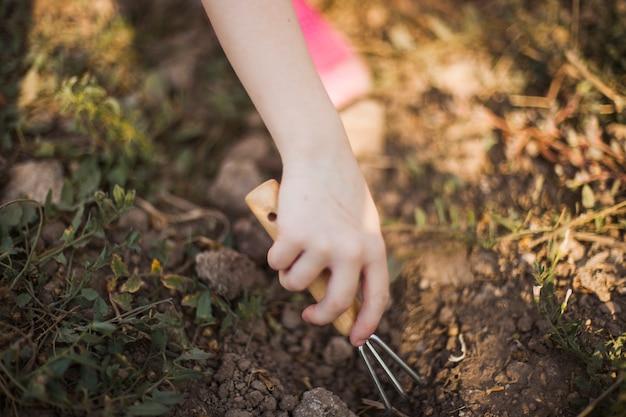 Nahaufnahme der hand den boden mit gartenarbeitgabel gräbend