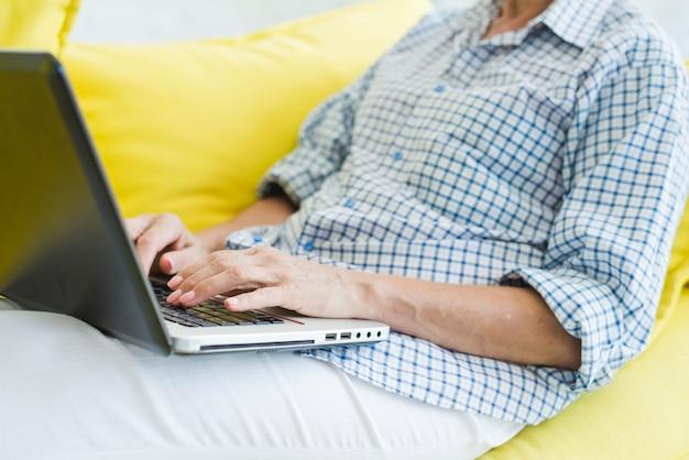 Nahaufnahme der hand der älteren frau, die auf laptop schreibt