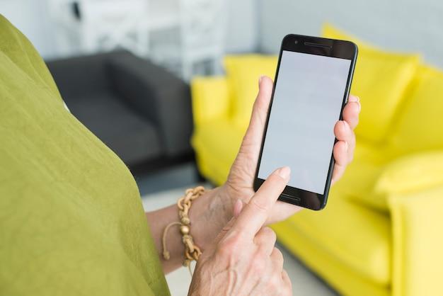 Nahaufnahme der hand der älteren frau, die mobiltelefonschirm berührt