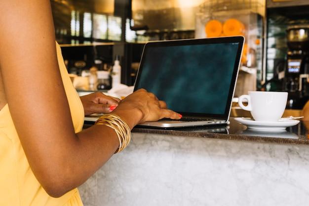 Nahaufnahme der hand der frau, die auf digitaler tablette am café schreibt