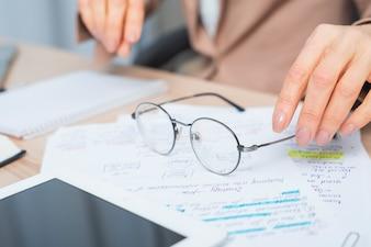 Nahaufnahme der Hand der Frau, die Brillen über dem Dokument hält