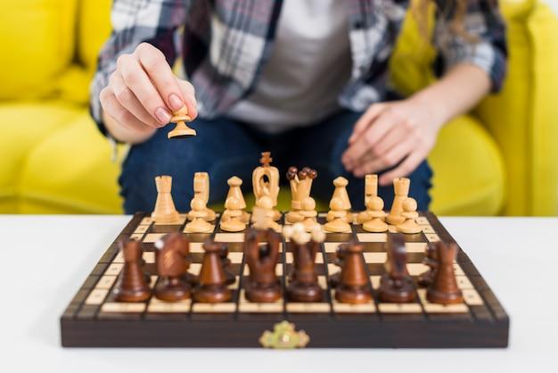 Nahaufnahme der hand der frau, die das schach spielt