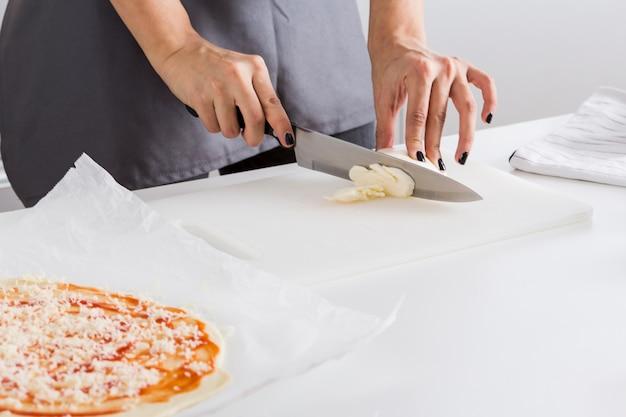 Nahaufnahme der hand der frau, die den käse mit messer auf hackendem brett schneidet