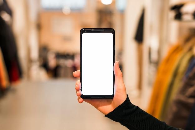 Nahaufnahme der hand der frau, die ihr intelligentes telefon mit weißer bildschirmanzeige zeigt