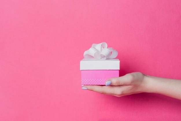 Nahaufnahme der hand der frau, die kasten mit weißem bandbogen auf rosa hintergrund hält
